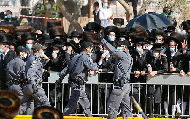 """La police tente d'éloigner les Haredim venus participer aux funérailles du rabbin Mordechai Leifer, le """"rabbin de Pittsburgh"""", à Ashdod, le 5 octobre 2020. (Crédit :Flash90)"""