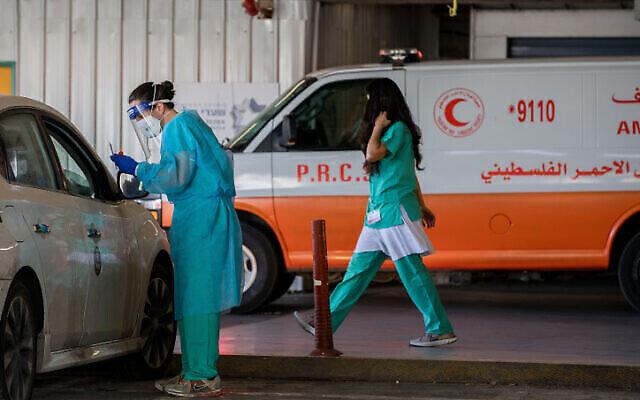 Un membre du personnel médical du centre médical Shaare Zedek de Jérusalem en équipement de protection effectue un prélèvement pour un test de COVID-19 le 8 octobre 2020. (Nati Shohat / Flash90)