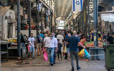Des gens font leur marché à Ramlé, dans le centre du pays, le 16 octobre 2020. (Crédit : Yossi Aloni/Flash90)