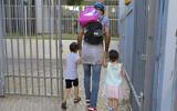 Des parents accompagnent leurs enfants dans un jardin d'enfants à Tel Aviv, lors de leur réouverture le 18 octobre 2020, après avoir été fermés lors d'un confinement national visant à prévenir la propagation du Coronavirus. (Avshalom Sassoni/Flash90)