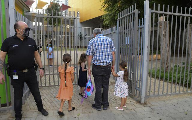 Des parents accompagnent leurs enfants au jardin d'enfants à Tel Aviv après l'allègement du confinement national pour cause de coronavirus, le 18 octobre 2020 (Crédit : Avshalom Sassoni/Flash90)