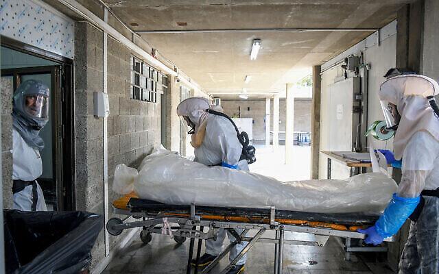 """Des employés de la """"Hevra Kadisha"""", la société officielle israélienne d'inhumation des juifs, préparent un corps dans une morgue spéciale pour les victimes de coronavirus, à Holon, le 28 octobre 2020. (Flash90)"""
