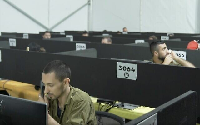 Illustration : dans une vidéo publiée par l'Armée de défense d'Israël le 29 juillet 2020, des soldats travaillent par téléphone au siège du commandement du front intérieur de Tsahal lors d'une visite du tsar du coronavirus, le professeur Ronni Gamzu. (Capture d'écran : Armée de défense d'Israël)