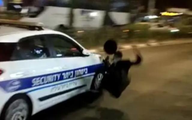 Une voiture de sécurité municipale s'éloigne en percutant un haredi qui manifestait contre le prolongement du confinement dans la ville de Beitar Illit, le 15 octobre 2020. (Capture d'écran /Twitter)