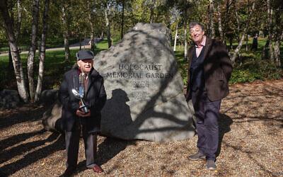 Le survivant de la Shoah et double participant aux JO, Sir Ben Helfgott, reçoit son prix Pride of Britain des mains de Stephen Fry près du mémorial de la Shoah de Hyde Park, à Londres, en octobre 2020. (Crédit : Philip Coburn/ via Jewish news)