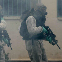 Des soldats de Tsahal en combinaison de protection chimique organisent un exercice simulant une attaque chimique dans le cadre d'un exercice national de défense civile à Ramat Gan, près de Tel Aviv, le 20 mars 2007. (Roni Schutzer/Flash90)