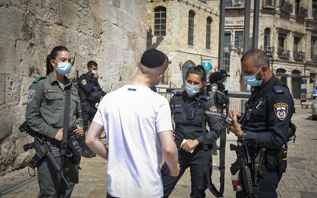 La police donne à un homme une amende pour avoir violé les règles nationales de confinement à la porte de Jaffa dans la vieille ville de Jérusalem le 24 septembre 2020. (Olivier Fitoussi/Flash90)