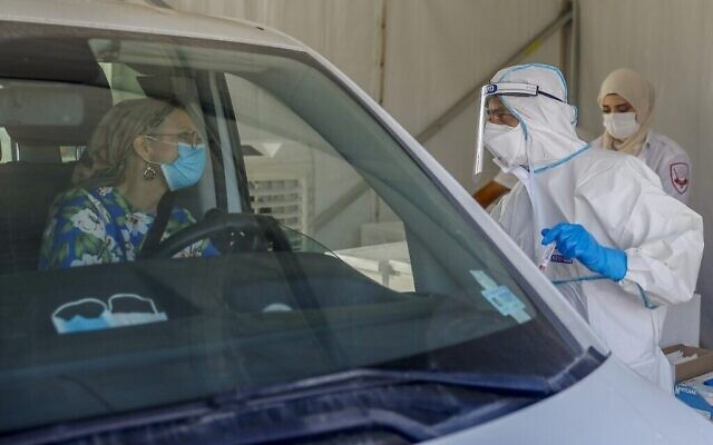 Un ambulancier des services médicaux israéliens du Magen David Adom s'entretient avec un chauffeur dans un centre de test COVID-19 au volant à Jérusalem, le 7 octobre 2020. (AHMAD GHARABLI / AFP)