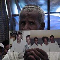 Un fidèle éthiopien à la synagogue d'Addis-Abeba priant et tenant des photos de membres de sa famille vivant en Israël. (Bernard Dichek/ Times of Israel)