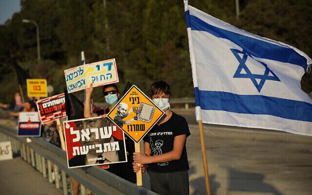 Des militants manifestent contre le Premier ministre Benjamin Netanyahu sur la route 3, dans le centre d'Israël, le 10 octobre 2020 (Nati Shohat/Flash90)