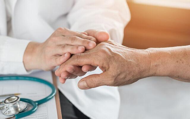 Un praticien rassure un patient agé. (Crédit : Chinnapong, iStock by Getty Images)