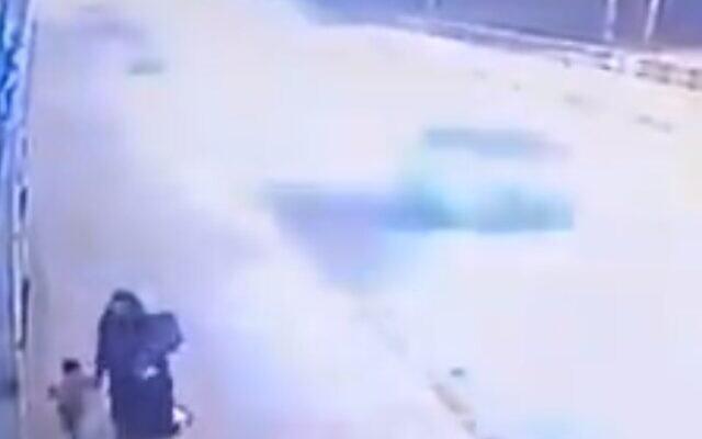 Capture d'écran d'une vidéo de surveillance CCTV où l'on voit une femme marcher avec ses deux enfants sur un pont avant de les jeter par dessus bord dans le fleuve Tigre. (Capture d'écran)