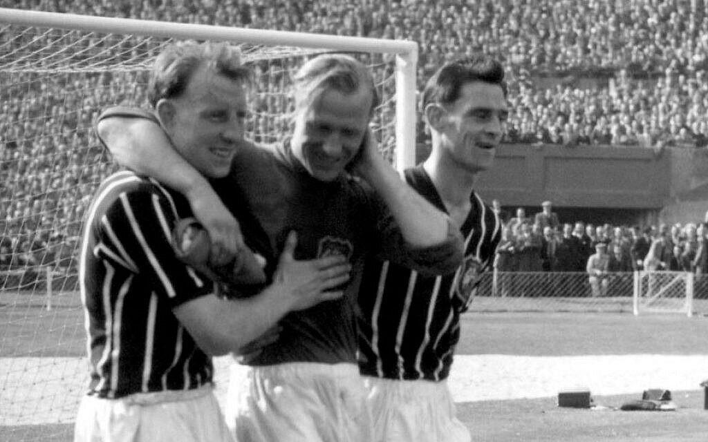Photo du 5 mai 1956 tirée des dossiers de Bernd Trautmann, plus connu sous le nom de Bert, gardien de but de Manchester City né en Allemagne, au centre, assisté depuis le terrain par deux joueurs non identifiés, souffrant d'une fracture du cou, lors de la finale de la FA Cup contre Birmingham, au stade de Wembley à Londres. (Crédit photo : AP/PA, Dossier)