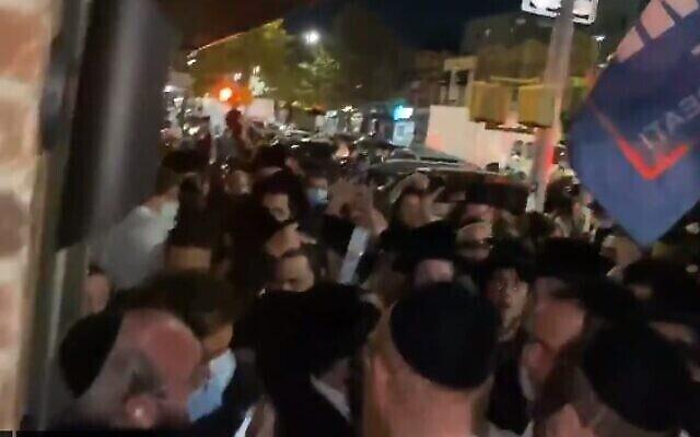 Le journaliste juif Jacob Kornbluh (en bas à gauche) entouré par des dizaines de manifestants ultra-orthodoxes à Brooklyn le 7 octobre 2020. (Capture d'écran / Twitter)