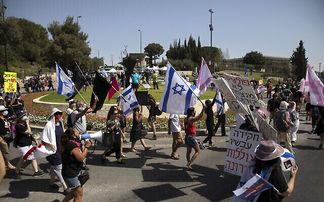 Des manifestants agitent des drapeaux et scandent des slogans lors d'une manifestation contre une mesure proposée pour réduire les manifestations publiques pendant le confinement national actuel en raison de la pandémie de coronavirus, devant la Knesset, à Jérusalem, le 29 septembre 2020. (Sebastian Scheiner/AP)