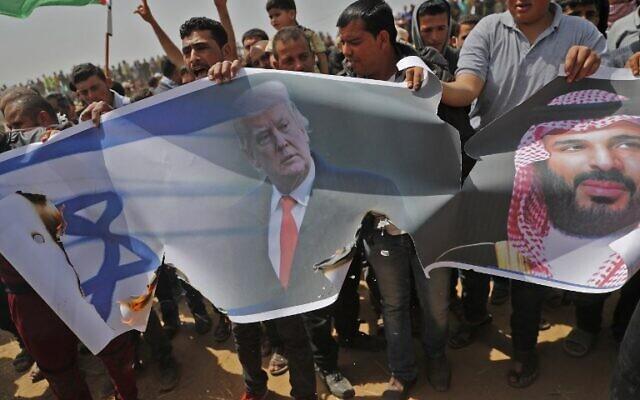 Les Palestiniens s'apprêtent à incendier un drapeau israélien et des portraits du président américain Donald Trump et du prince héritier saoudien Mohammed ben Salmane lors d'une manifestation contre la barrière frontalière avec Israël, à l'est de Khan Younès, au sud de Gaza, le 13 avril 2018. (Crédit : AFP PHOTO / Thomas COEX)