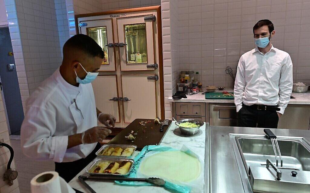 Le rabbin Yaakov Eisenstein, à droite, supervise la préparation des plats au Elli's Kosher Kitchen, à Dubaï, le 5 octobre 2020. (Crédit :  GIUSEPPE CACACE / AFP)