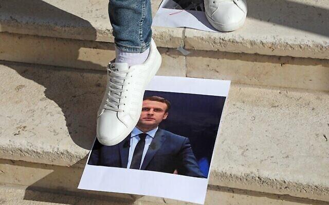 Un Palestinian marche sur une photo du président français Emmanuel Macron lors d'une manifestation contre lui à l'université d'al-Aroub, au nord de la ville de Hébron, le 27 octobre 2020. (Crédit : Hazem Bader/AFP)
