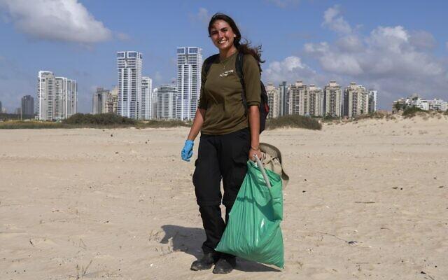 Lotem Benbenishti, 28 ans, a trouvé du travail dans la collecte de déchets sur la plage Poleg de Netanya, le 21 octobre 2020. (Crédit : MENAHEM KAHANA / AFP)