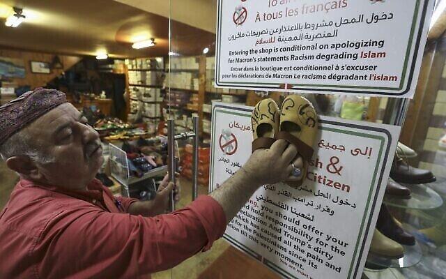 Un cordonnier palestinien, Imad Mohammad, et ses chaussures ornées des noms des présidents français et américains en calligraphie arabe, dans sa boutique de Ramallah, le 30 octobre 2020. (Crédit : Abbas Momani/AFP)