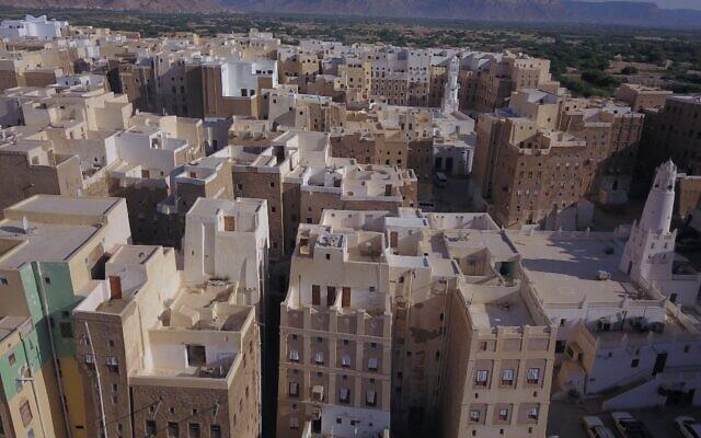 """Photo aérienne prise le 17 octobre 2020 de la ville de Shibam, dans le gouvernorat central de l'Hadramawt au Yémen, avec en arrièrere-plan ce qui ressemble au Grand Canyon. Shibam, le """"Manhattan du désert"""" du Yémen, a été largement épargné par la guerre mais reste à la merci des catastrophes naturelles. (Crédit : AFP)"""