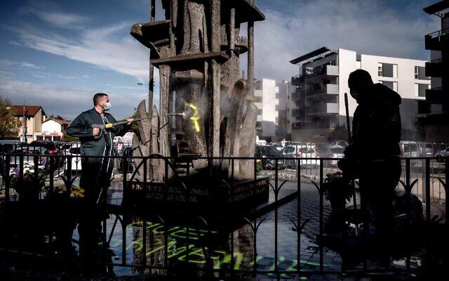 Un homme nettoie un mémorial du génocide arménien à Décines-Charpieu, près de Lyon, le 1er novembre 2020, sur lequel un message anti-Arméniens a été tagué par des nationalistes turcs. (Crédit : JEFF PACHOUD / AFP)
