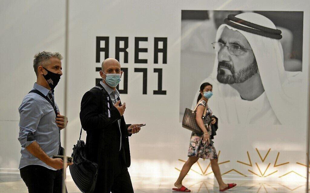 Les membres d'une délégation israélienne de high-tech passent devant une affiche du dirigeant de Dubaï, le cheikh Mohammed bin Rashid al-Maktoum, lors d'une réunion avec leurs homologues émiratis au siège des Accélérateurs d'avenir de Dubaï, le 27 octobre 2020. (Karim Sahib/AFP)
