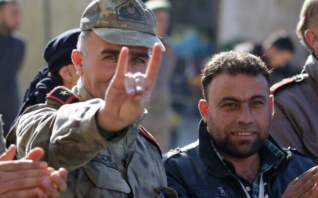 Un homme vêtu d'un uniforme d'officier turc fait le signe des Loups gris (une organisation ultranationaliste d'extrême droite turque), lors d'une manifestation en soutien à la Turquie voisine dans la ville syrienne de Bizaa, au nord d'Alep, le 21 décembre 2018. (Crédit : Bakr ALKASEM / AFP)