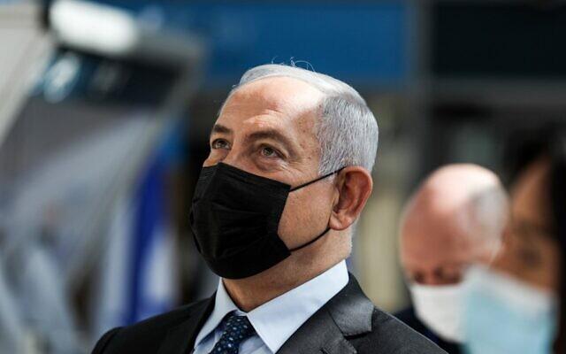 Benjamin Netanyahu, masqué, assiste à l'inauguration d'une station de dépistage de la COVID-19 à l'aéroport international Ben Gurion de Lod, le 9 novembre 2020. (Crédit : ATEF SAFADI / POOL / AFP)