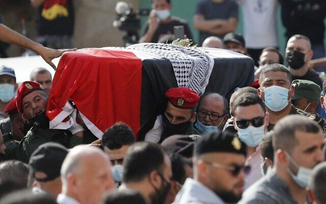 Des Palestiniens et des gardes d'honneur transportent le cercueil de Saeb Erekat pendant la procession de ses funérailles à Jéricho, en Cisjordanie, le 11 novembre 2020. (Crédit : Ahmad GHARABLI / PPO / AFP)
