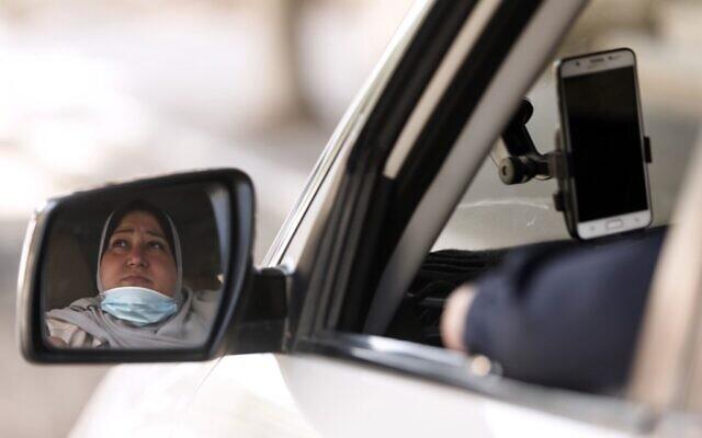 Nayla Abou Jubbah, première femme chauffeur de taxi à Gaza, dans son véhicule, le 17 novembre 2020. (Crédit : MAHMUD HAMS / AFP)