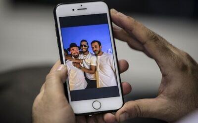 Un homme au Caire tient un téléphone montrant une photo du chanteur égyptien Mohamed Ramadan publiée par la page Facebook officielle de l'État d'Israël en arabe (liée au ministère des Affaires étrangères) montrant Ramadan (au centre) enlaçant le chanteur israélien Omer Adam (à gauche) sur un toit de Dubaï, le 22 novembre 2020. (Crédit : Khaled DESOUKI / AFP)