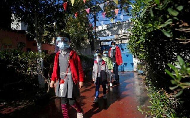 Des enfants palestiniens vont à l'école, masqués en pleine pandémie de Covd-19, le 23 novembre 2020. (Crédit : Mohammed ABED / AFP)