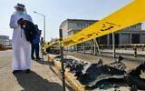 Un homme, masqué en raison de la pandémie de coronavirus COVID-19, parcourt son téléphone alors qu'il se tient près des débris suite à l'attaque de l'installation pétrolière Saudi Aramco à Djeddah, en Arabie Saoudite, le 24 novembre 2020. (FAYEZ NURELDINE / AFP)