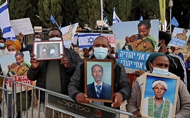 Des membres de la communauté éthiopienne israélienne brandissent des photos de leurs proches devant le bureau du Premier ministre à Jérusalem, le 25 novembre 2020. (Menahem Kahana / AFP)