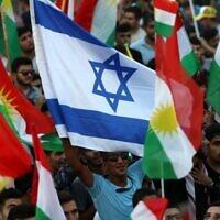 (Archives) Photo prise le 16 septembre 2017, des Kurdes irakiens agitent un drapeau israélien et des drapeaux kurdes lors d'un événement exhortant les gens à voter lors du prochain référendum sur l'indépendance à Arbil, la capitale de la région kurde autonome du nord de l'Irak. (Crédit : SAFIN HAMED / AFP)