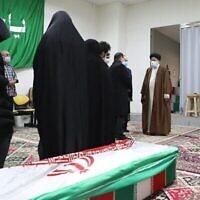 Le chef du pouvoir judiciaire, l'ayatollah Ebrahim Raisi (D), salue la dépouille du scientifique assassiné Mohsen Fakhrizadeh entouré de sa famille, à Téhéran le 28 novembre 2020. (Crédit : MIZAN NEWS AGENCY / AFP)