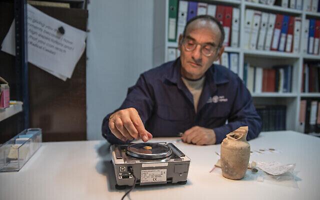Le docteur Robert Kool pèse les pièces d'or découvertes près du mur Occidental de Jérusalem. (Crédit : Shai Halevit, Autorité israélienne des antiquités)