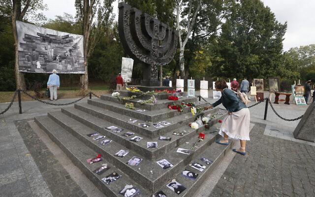 Une femme dépose des fleurs sur un monument près du ravin de Babi Yar où des dizaines de milliers de Juifs ont été tués pendant la Seconde Guerre mondiale, à Kiev, en Ukraine, le 29 septembre 2020. (Crédit : AP Photo/Efrem Lukatsky)