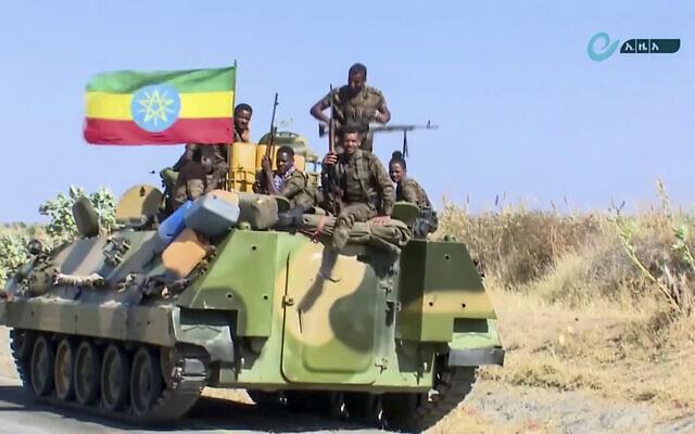 Capture d'écran d'une vidéo non datée publiée par l'agence de presse éthiopienne, le 16 novembre 2020, montrant des militaires éthiopiens assis sur un véhicule blindé de transport de troupes à côté d'un drapeau national, sur une route dans une zone proche de la frontière des régions du Tigré et d'Amhara en Éthiopie. (Crédit : Agence de presse éthiopienne via AP)