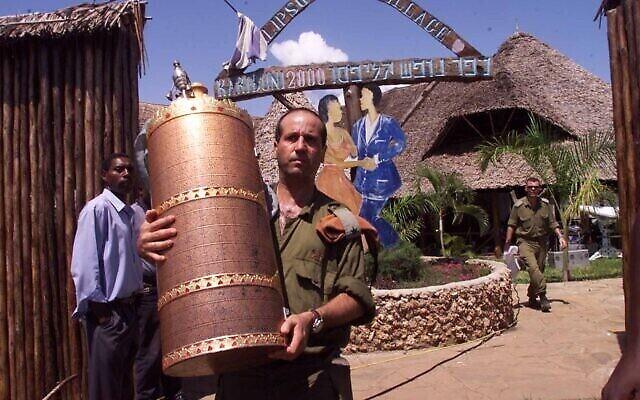 Un soldat israélien enlève un rouleau de la Torah de l'hôtel Paradise, propriété d'Israël, le vendredi 29 novembre 2002, à Kikambala, près de Mombassa, au Kenya. L'explosion de l'hôtel Paradise a tué 10 Kenyans, trois Israéliens et les trois kamikazes. (AP Photo/Karel Prinsloo)