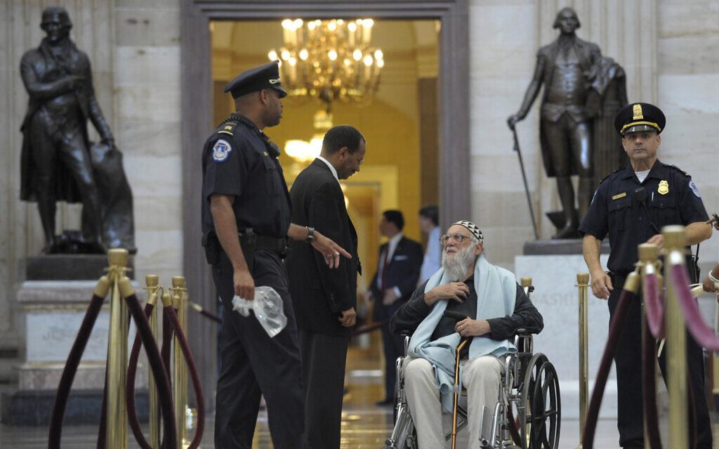 Le rabbin Arthur Waskow attend d'être arrêté par la police  lors d'une manifestation contre des coupes budgétaires devant le Capitole à Washington, le 28 juillet 2011. (Crédit :   AP Photo/Susan Walsh)
