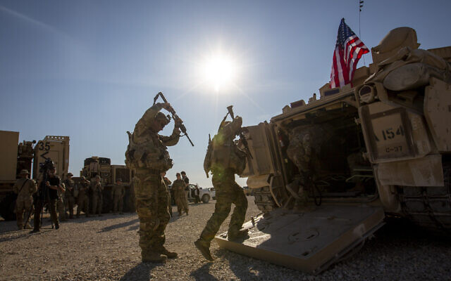 Des membres d'équipage américains pénètrent dans des véhicules de combat Bradley sur une base militaire américaine située dans un endroit non divulgué au nord-est de la Syrie, le 11 novembre 2019. (AP Photo/Darko Bandic)