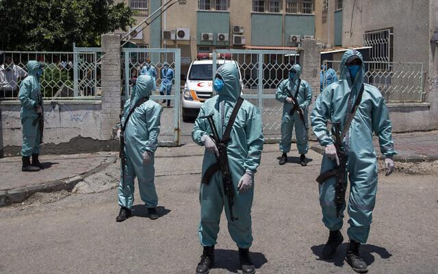 Des policiers palestiniens du Hamas portent des combinaisons de protection alors qu'ils participent à une simulation d'éventuelles infections de coronavirus dans la ville de Gaza, le samedi 18 juillet 2020. (Crédit : AP/Khalil Hamra)