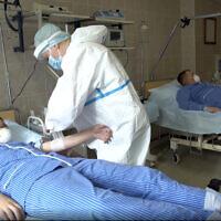 Des travailleurs médicaux prélèvent le sang de volontaires participant à un essai d'un vaccin contre le coronavirus à l'hôpital militaire principal de Budenko, près de Moscou, en Russie, le 15 juillet 2020. (Service de presse du ministère russe de la Défense via AP)