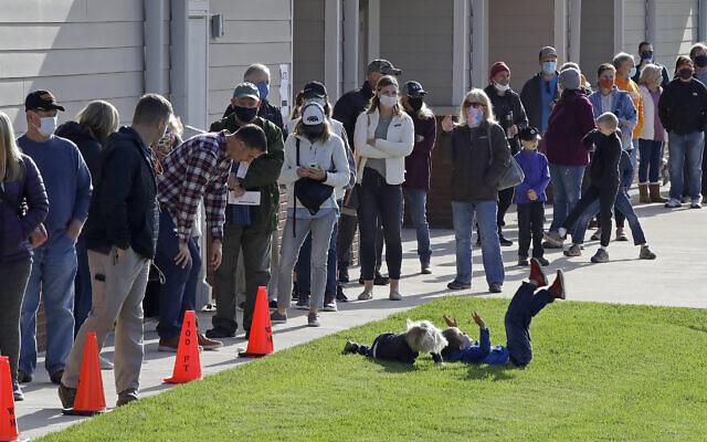 Des enfants jouent pendant que des électeurs font la queue pour déposer leur bulletin de vote au bâtiment du Waldens Ridge Emergency Services le jour du scrutin, le mardi 3 novembre 2020, à Walden, Tenn. (AP/Ben Margot)