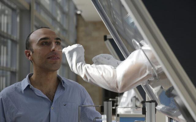 Un technicien fait une démonstration d'un prélèvement en vue d'un test coronavirus sur un employé de l'aéroport Ben-Gurion au centre de dépistage installé dans l'aéroport, à Tel Aviv, le 9 novembre 2020. (Crédit :  AP Photo/Maya Alleruzzo)
