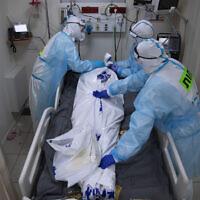 Des personnels médicaux portant des équipements de protection recouvrent la dépouille d'un homme décédé des suites de la COVID-19 dans l'unité pour soins intensifs mise en place pour les malades du coronavirus au centre médical Shaare Zedek de Jérusalem, le 23 novembre 2020. (Crédit : AP Photo/Oded Balilty)