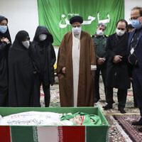 L'Ayatollah Ebrahim Raisi , responsable du système judiciaire iranien, rend hommage au scientifique assassiné Mohsen Fakhrizadeh en compagnie de sa famille à Téhéran, en Iran, le 28 novembre 2020. (Crédit : Agence de presse Mizan via AP)