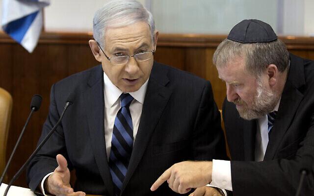 Le Premier ministre Benjamin Netanyahu, à gauche, s'entretient avec le secrétaire du cabinet de l'époque Avichai Mandelblit lors de la réunion hebdomadaire du cabinet à Jérusalem, le 21 septembre 2014. (Crédit : AP / Menahem Kahana, Pool / File)